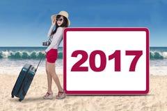 Mujer con los números 2017 en la playa Imagen de archivo libre de regalías