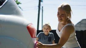 Mujer con los niños que lavan el coche almacen de video
