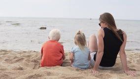 Mujer con los niños que se sientan en la playa almacen de video