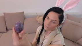 Mujer con los oídos del conejito que guardan el huevo de Pascua y que se sientan en el sofá