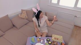Mujer con los oídos del conejito que preparan los huevos de Pascua