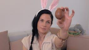 Mujer con los oídos del conejito y el huevo de Pascua