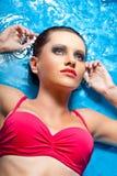Mujer con los ojos ahumados que ponen en agua Fotografía de archivo libre de regalías