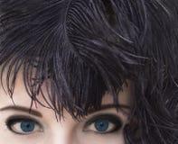 Mujer con los ojos azules profundos en tocado negro de la pluma Maquillaje ahumado de los ojos Fotografía de archivo