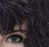 Mujer con los ojos azules profundos en tocado negro de la pluma Maquillaje ahumado de los ojos Fotos de archivo