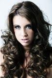 Mujer con los ojos azules y el pelo rizado largo Imagen de archivo