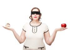 Mujer con los ojos vendados del tamaño extra grande que elige entre la manzana y la torta Fotografía de archivo