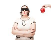 Mujer con los ojos vendados del tamaño extra grande temptating con la manzana Fotografía de archivo libre de regalías
