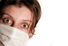 Mujer con los ojos verdes grandes que llevan la máscara médica imagenes de archivo