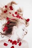 Mujer con los pétalos color de rosa en su pelo Foto de archivo