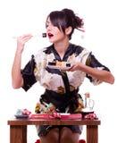 Mujer con los palillos y el rodillo de sushi Imagen de archivo libre de regalías