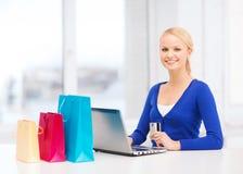 Mujer con los panieres, el ordenador portátil y la tarjeta de crédito Foto de archivo libre de regalías