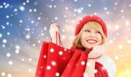 Mujer con los panieres rojos sobre fondo de la nieve imágenes de archivo libres de regalías