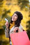 Mujer con los panieres y tarjeta de crédito en otoño Fotografía de archivo