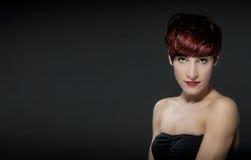 Mujer con los pelos rojos delante de un fondo gris Fotografía de archivo