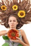 Mujer con los pelos y el girasol largos Foto de archivo