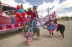 Mujer con los perros patrióticos en el cuarto del desfile de julio, en Lima Montana Imágenes de archivo libres de regalías