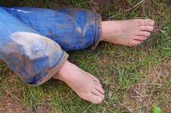 Mujer con los pies desnudos y los vaqueros fangosos Fotografía de archivo