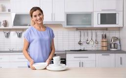 Mujer con los platos limpios cerca de la tabla en cocina fotos de archivo