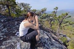 Mujer con los prismáticos en una montaña Foto de archivo libre de regalías