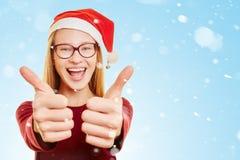 Mujer con los pulgares para arriba en la nieve en la Navidad Imagen de archivo libre de regalías