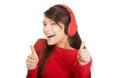 Mujer con los pulgares para arriba que escucha la música Fotografía de archivo