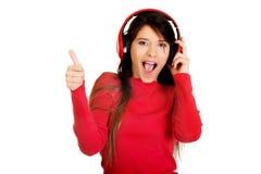 Mujer con los pulgares para arriba que escucha la música Fotografía de archivo libre de regalías