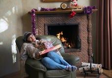 Mujer con los regalos de la Navidad por la chimenea Imagen de archivo