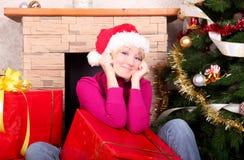 Mujer con los regalos de Navidad que desgastan el sombrero de santa foto de archivo