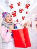 Mujer con los regalos después de hacer compras al Año Nuevo en la tienda Fotografía de archivo