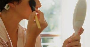 Mujer con los rodillos del pelo que aplican el maquillaje 4K 4k metrajes