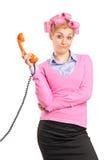 Mujer con los rodillos del pelo que sostienen un tubo del teléfono Foto de archivo libre de regalías