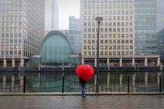 Mujer con los soportes de paraguas rojos, en forma de corazón en Londres Canary Wharf fotos de archivo libres de regalías