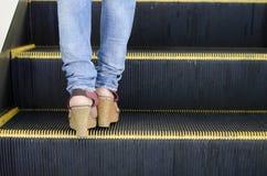 Mujer con los tacones altos y la mezclilla que se colocan en la escalera móvil foto de archivo libre de regalías