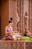Mujer con los vestidos tradicionales que doblan el pétalo del loto Fotos de archivo libres de regalías