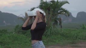 Mujer con los vidrios de VR en el punto de vista tropical metrajes