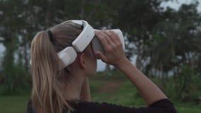 Mujer con los vidrios de VR en el punto de vista tropical almacen de metraje de vídeo