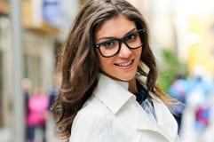 Mujer con los vidrios del ojo que sonríe en fondo urbano Fotos de archivo libres de regalías