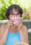 Mujer con los vidrios que bebe una taza de té Imagen de archivo