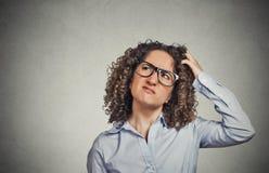 Mujer con los vidrios que rasguñan la cabeza, pensamiento confundido Fotografía de archivo