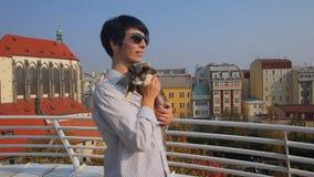 Mujer con los vidrios que sostienen un gato en sus brazos metrajes
