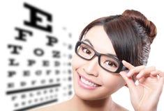 Mujer con los vidrios y la carta de prueba del ojo Imagen de archivo