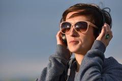 Mujer con música que escucha de las gafas de sol en auriculares en Imagen de archivo