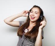 Mujer con música que escucha de los auriculares Agains del baile de la muchacha de la música Foto de archivo