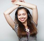 Mujer con música que escucha de los auriculares Agains del baile de la muchacha de la música Imagen de archivo