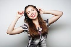Mujer con música que escucha de los auriculares Agains del baile de la muchacha de la música Imagen de archivo libre de regalías
