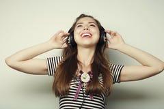 Mujer con música que escucha de los auriculares Agains del baile de la muchacha de la música Fotos de archivo libres de regalías