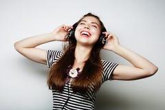 Mujer con música que escucha de los auriculares Agains del baile de la muchacha de la música Foto de archivo libre de regalías