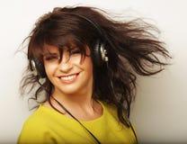 Mujer con música que escucha de los auriculares Baile de la muchacha de la música contra el fondo blanco Fotografía de archivo libre de regalías