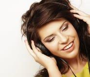 Mujer con música que escucha de los auriculares Baile de la muchacha de la música contra el fondo blanco Imagenes de archivo